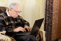 Hombre mayor que mecanografía en su ordenador portátil imagen de archivo libre de regalías
