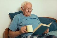 Hombre mayor que miente en el libro del malo y de lectura imagen de archivo