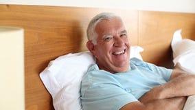 Hombre mayor que miente en la cama que sonríe en la cámara metrajes