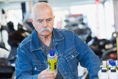 Hombre mayor que mira el espray del lubricante del autom?vil fotografía de archivo libre de regalías