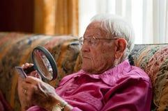 Hombre mayor que mira el objeto con la lupa Imágenes de archivo libres de regalías