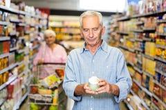 Hombre mayor que mira la comida enlatada Imagenes de archivo