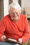 Hombre mayor que mira la fotografía en marco Foto de archivo libre de regalías