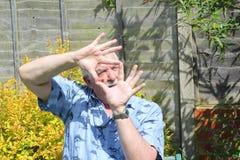 Hombre mayor que mira a través de sus fingeres Imagenes de archivo
