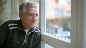 Hombre mayor que mira a través de ventana almacen de metraje de vídeo
