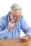 Hombre mayor que mira un teléfono Imagen de archivo libre de regalías