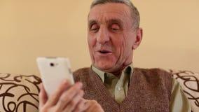 Hombre mayor que mira y que mueve de un tirón a través de las fotos en su smartphone almacen de metraje de vídeo