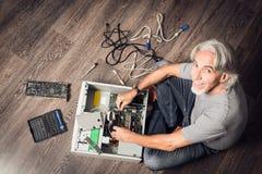 Hombre mayor que monta un equipo de escritorio Fotos de archivo libres de regalías