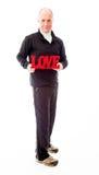 Hombre mayor que muestra un texto rojo del amor Imágenes de archivo libres de regalías