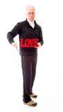 Hombre mayor que muestra un texto rojo y los pulgares del amor abajo Imagen de archivo