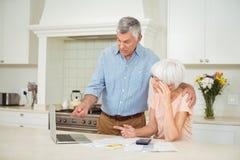 Hombre mayor que obra recíprocamente con la mujer mayor en cocina Fotos de archivo