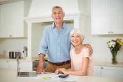 Hombre mayor que obra recíprocamente con la mujer mayor en cocina Imagen de archivo
