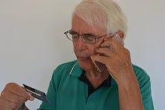 Hombre mayor que paga con una tarjeta de crédito sobre el teléfono fotografía de archivo libre de regalías