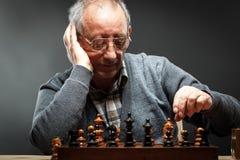 Hombre mayor que piensa en su próximo paso en un juego del ajedrez Imágenes de archivo libres de regalías