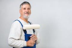 Hombre mayor que pinta una pared en su hogar Fotos de archivo libres de regalías