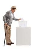 Hombre mayor que pone una votación en una caja de votación Fotografía de archivo