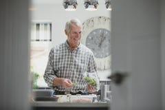 Hombre mayor que prepara la comida foto de archivo libre de regalías