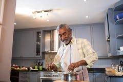 Hombre mayor que prepara la comida en cocina foto de archivo libre de regalías