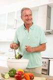 Hombre mayor que prepara la ensalada en cocina moderna Fotos de archivo libres de regalías