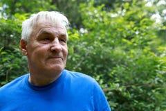Hombre mayor que presenta en el patio trasero Imagen de archivo libre de regalías