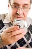 Hombre mayor que pulsa en el teléfono móvil Fotos de archivo