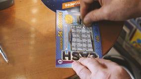 Hombre mayor que rasguña el boleto de lotería que gana efectivo premiado almacen de video