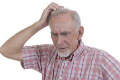 Hombre mayor que rasguña su cabeza Fotografía de archivo libre de regalías