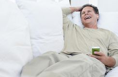 Hombre mayor que ríe mientras que música que escucha Fotografía de archivo libre de regalías