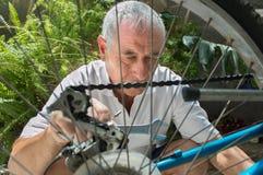 Hombre mayor que repara una bicicleta Imagen de archivo
