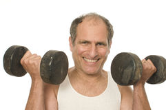 hombre mayor que resuelve pesos de la pesa de gimnasia Fotografía de archivo