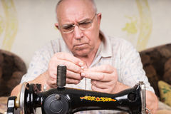 Hombre mayor que rosca la aguja de la máquina de coser Fotos de archivo libres de regalías