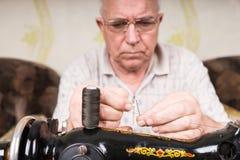 Hombre mayor que rosca la aguja de la máquina de coser Foto de archivo