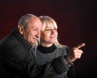 Hombre mayor que señala en algo a la mujer joven imagen de archivo