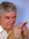 Hombre mayor que señala, guiñando y sonriendo Imagen de archivo libre de regalías