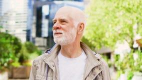 Hombre mayor que se coloca al aire libre Dictrict céntrico del negocio con los rascacielos y los árboles en fondo metrajes