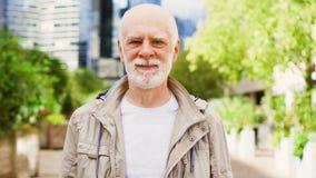 Hombre mayor que se coloca al aire libre Distrito financiero céntrico con los rascacielos y los árboles en fondo almacen de video