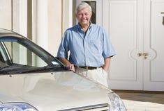 Hombre mayor que se coloca al lado del nuevo coche Foto de archivo libre de regalías