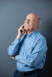 Hombre mayor que se coloca de pensamiento con una sonrisa feliz Foto de archivo libre de regalías