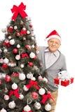 Hombre mayor que se coloca detrás de un árbol de navidad Foto de archivo