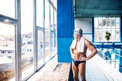 Hombre mayor que se coloca en una piscina interior Foto de archivo