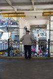 Hombre mayor que se levanta en el mercado de Bolhao en Oporto y que mira abajo de las tiendas y de la gente, Portugal Fotografía de archivo