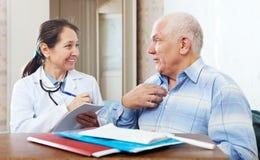 Hombre mayor que se queja al doctor cómodo Imagenes de archivo
