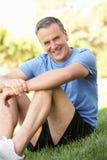 Hombre mayor que se reclina después de ejercitar en parque Imagen de archivo