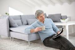 Hombre mayor que se relaja en casa leyendo la revista Fotos de archivo libres de regalías