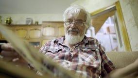 Hombre mayor que se relaja en casa y que mira el álbum con las fotos almacen de video