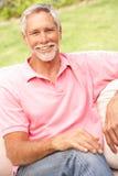 Hombre mayor que se relaja en jardín Foto de archivo