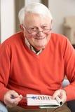 Hombre mayor que se relaja en silla en el país Imagen de archivo libre de regalías