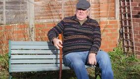 Hombre mayor que se relaja en un banco almacen de metraje de vídeo