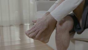 Hombre mayor que se relaja y que da masajes al pie cansado en casa que se sienta en el sofá metrajes