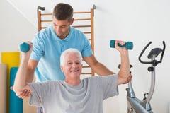 Hombre mayor que se resuelve con su instructor Fotografía de archivo